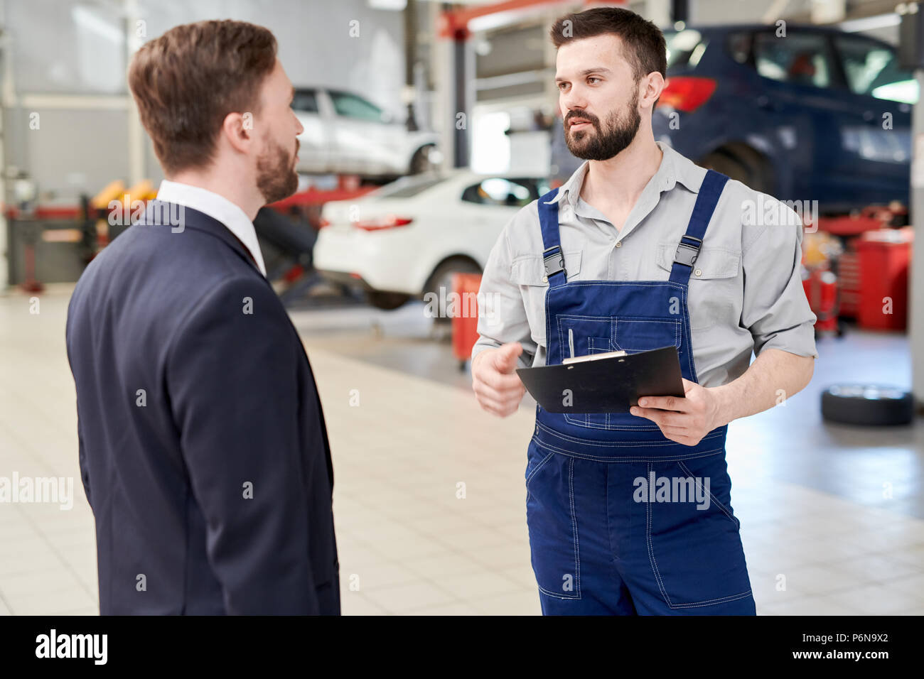 Modern Mechanic Talking to Client Stock Photo