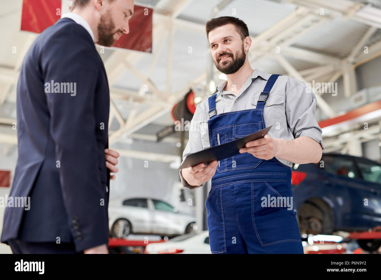 Smiling Mechanic Giving Contract to Client Stock Photo
