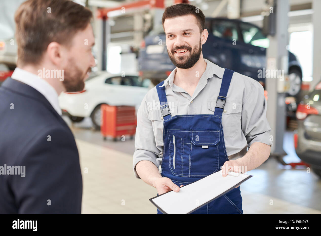 Mechanic Offering Contract to Client - Stock Image