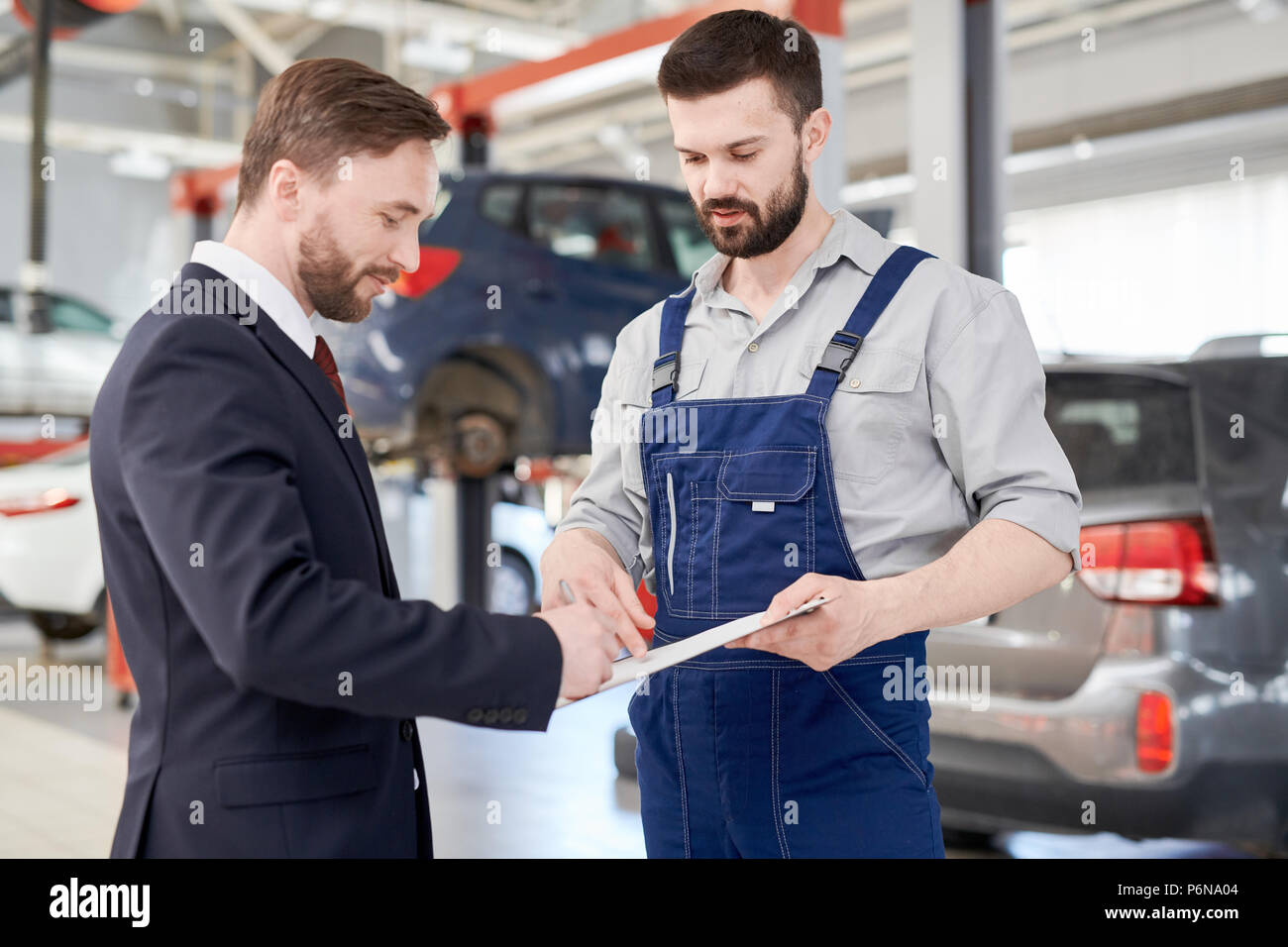 Businessman Signing Contract in Car Service - Stock Image