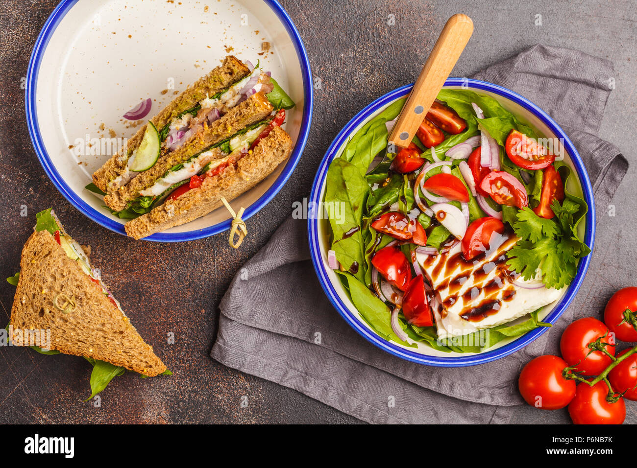 Bright summer salad with tomatoes, onions, balsamic and goat cheese with meat and cheese sandwiches. Food flat lay on dark background. - Stock Image