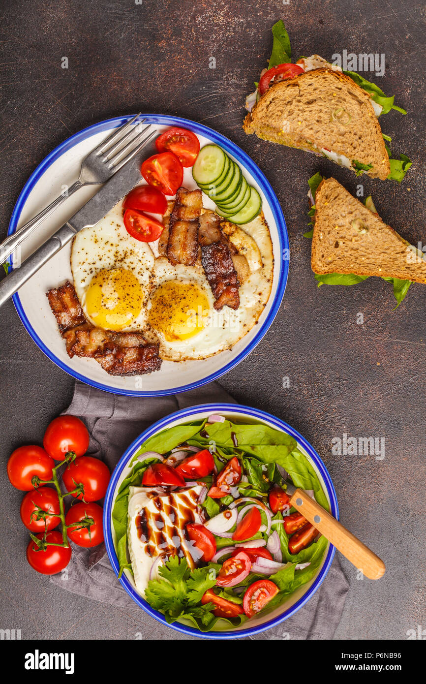 Food flat lay: vegetable salad with goat cheese, sandwiches with cheese and vegetables and fried eggs with bacon. Beautiful bright breakfast on a dark - Stock Image
