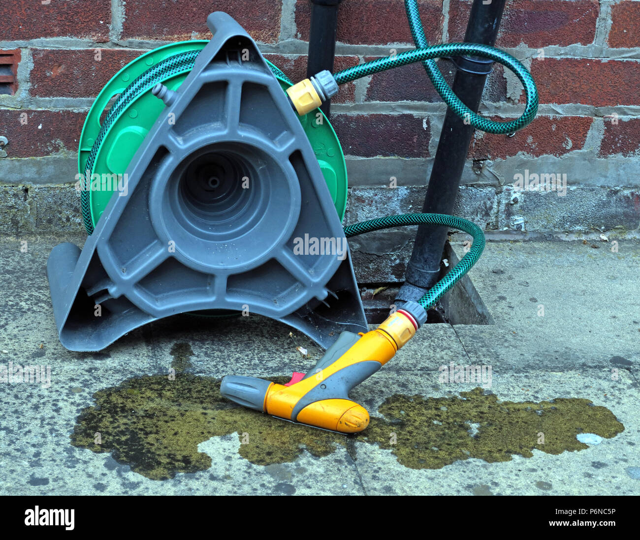 Hosepipe reel connected to a standpipe in garden, with leaking water - Stock Image