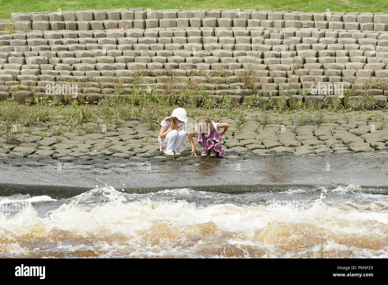 water safety, children playing near fast moving river Stock Photo
