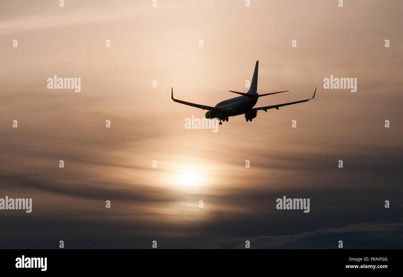 737 on final sunset approach to YVR with soft sunset as backdrop - Stock Image