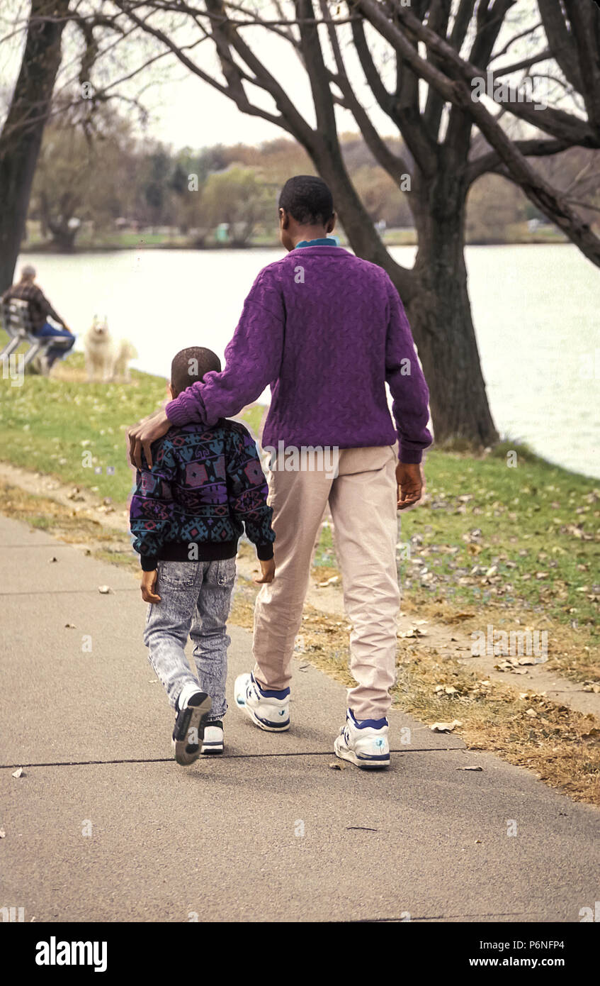 Sibling comforting Big brother walking with younger brother MR.  © Myrleen Pearson - Stock Image