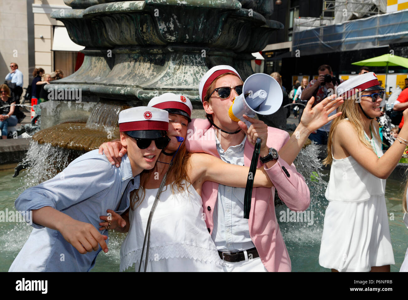 Danish students celebrate their high school graduation with the traditional dance round and plunge into the Stork Fountain on Stroeget in Copenhagen. Stock Photo