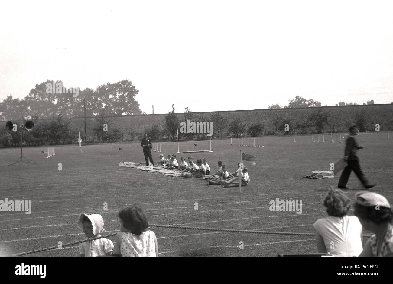 1950s, sack race at a primary school sports day...young children sitting down on the grass before the start of the traditional sack race, England, UK. - Stock Image