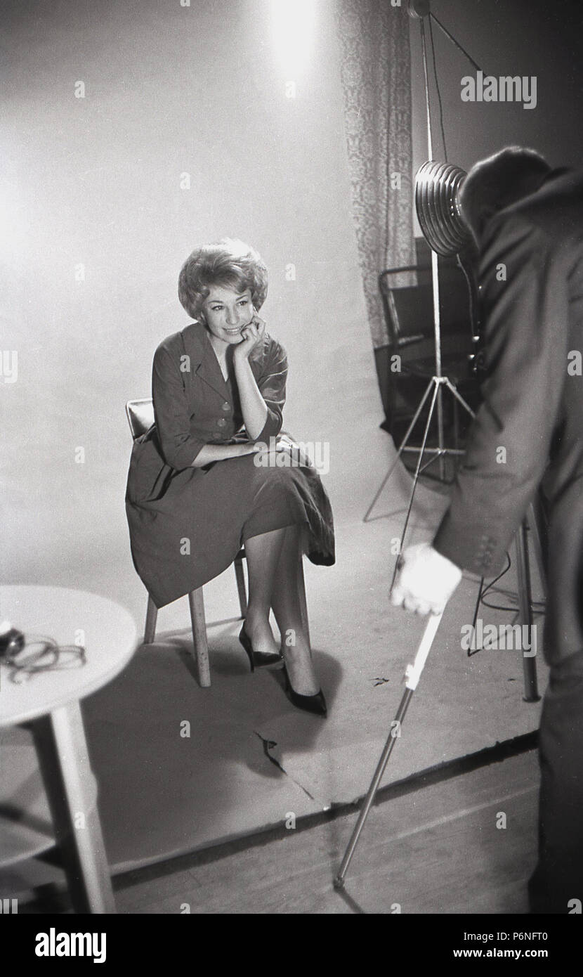 1950s, attractive, elgeant young lady with bouffant hairstyle sitting posing having her picture taken inside a professional photographic studio, England, UK. - Stock Image