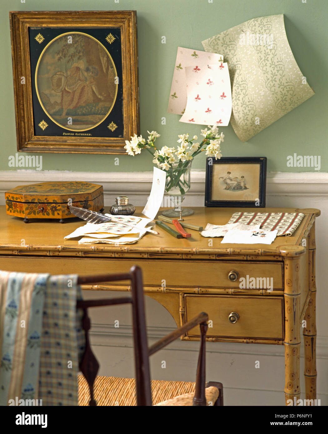 Picture Beside Wallpaper Samples On Wall Above Bamboo Desk And Antique Chair In Pale Green Study