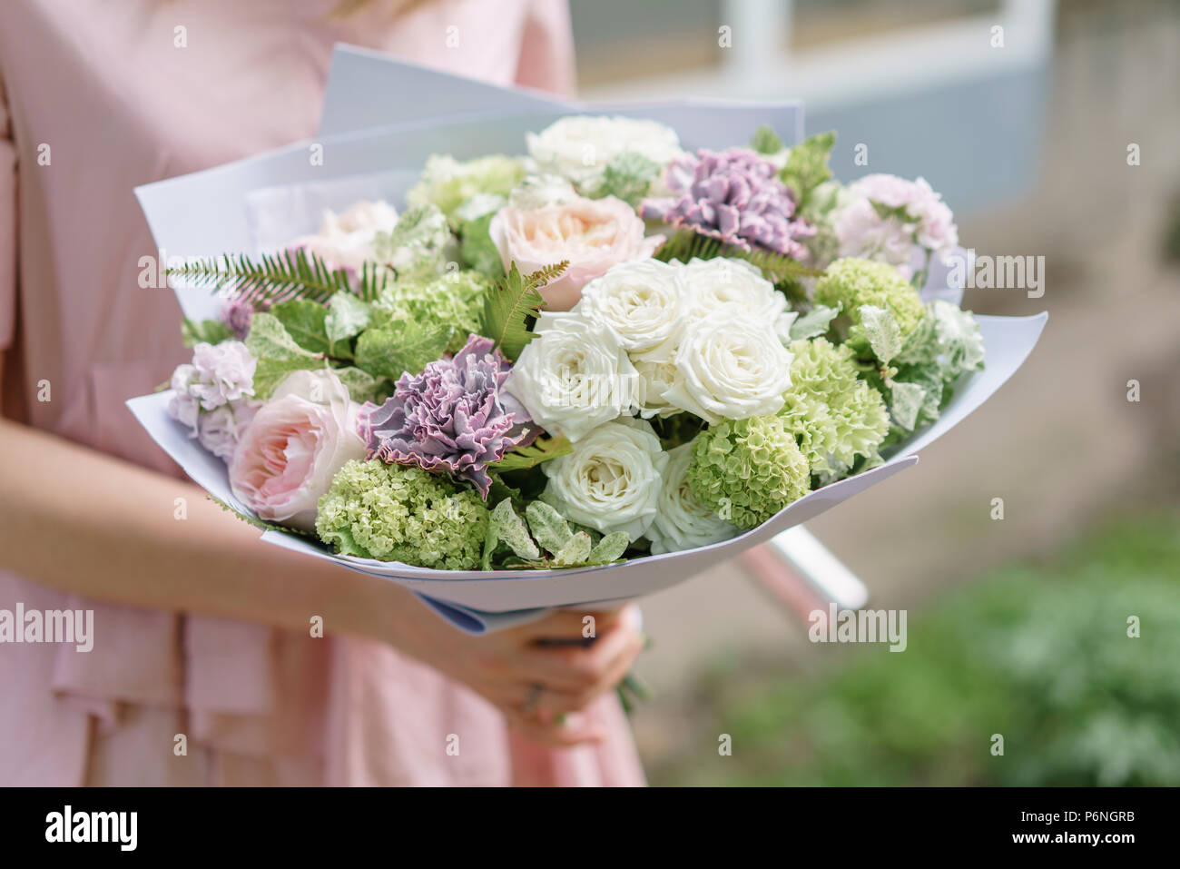 Young girl holding a beautiful summer bouquet flower arrangement young girl holding a beautiful summer bouquet flower arrangement with peonies the concept of a flower shop content for the catalog izmirmasajfo