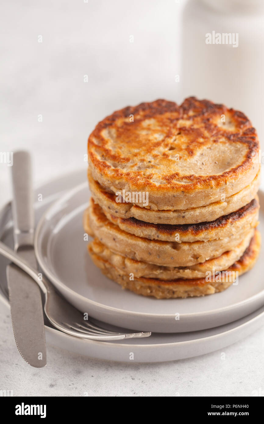 Vegan pancakes with chia seeds on a white plate, white background. Healthy vegan food concept. - Stock Image