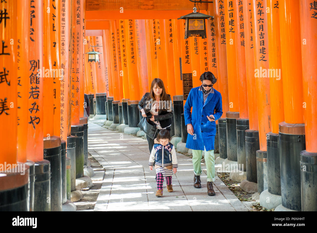 Japanese tourists explore Fushimi Inari Taisha in Kyoto, Japan. Along the main path there are more than 10000 torii gates. - Stock Image