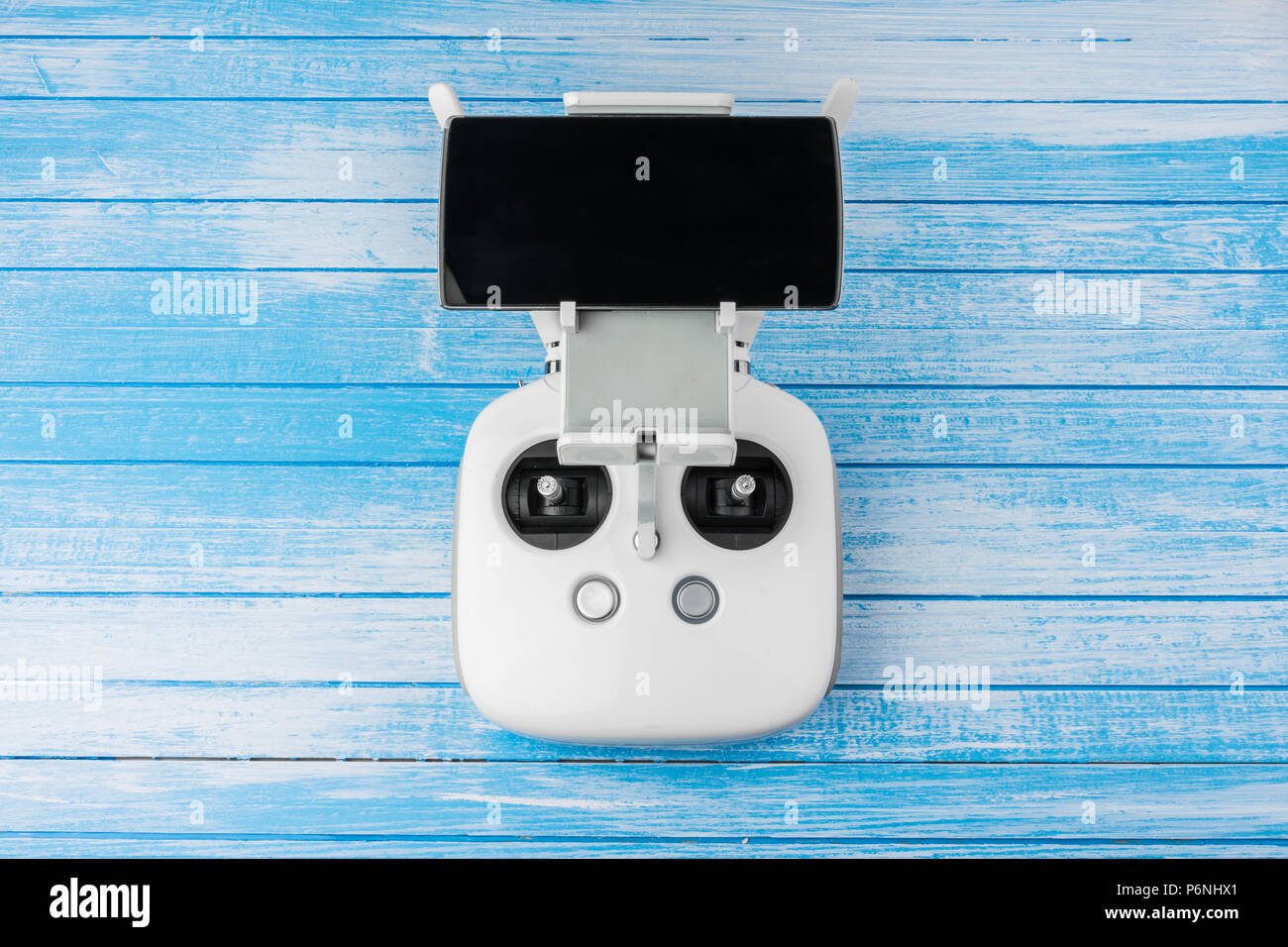 Modern High Tech White Drone Remote Controller With Smart Phone Antennas Connected And On Blue Wood Background Quadcopter Concept Top Angle