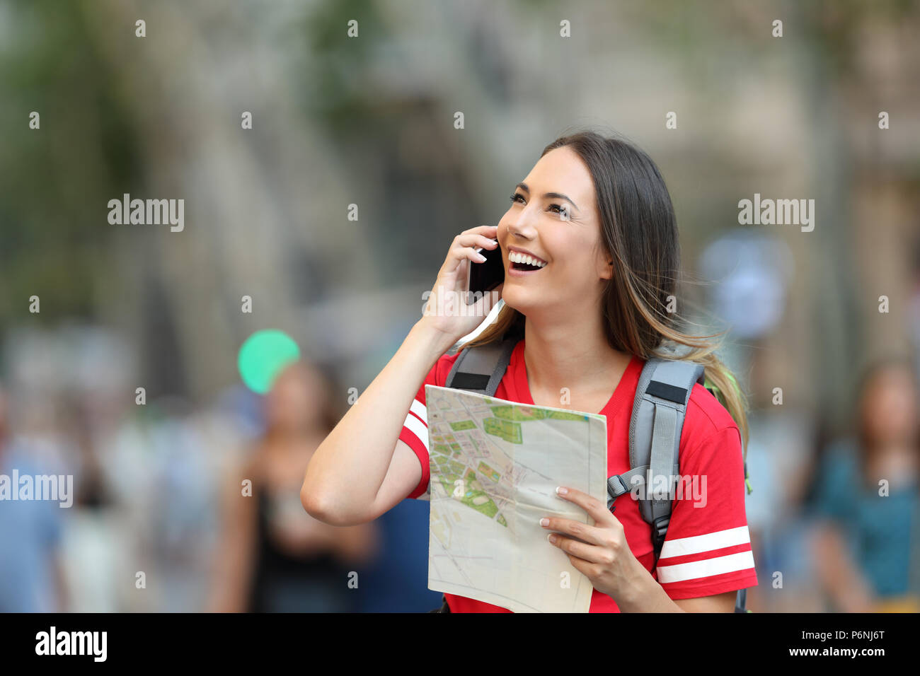 Happy teen tourist calling on phone in the street and looking above - Stock Image