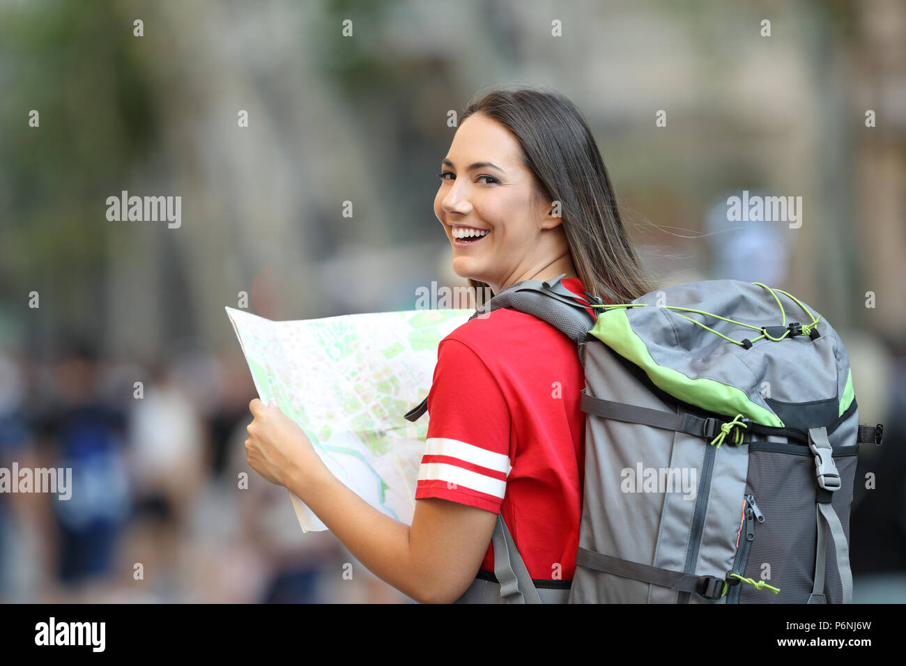 Happy teen tourist holding a paper guide and looking at camera on the street - Stock Image