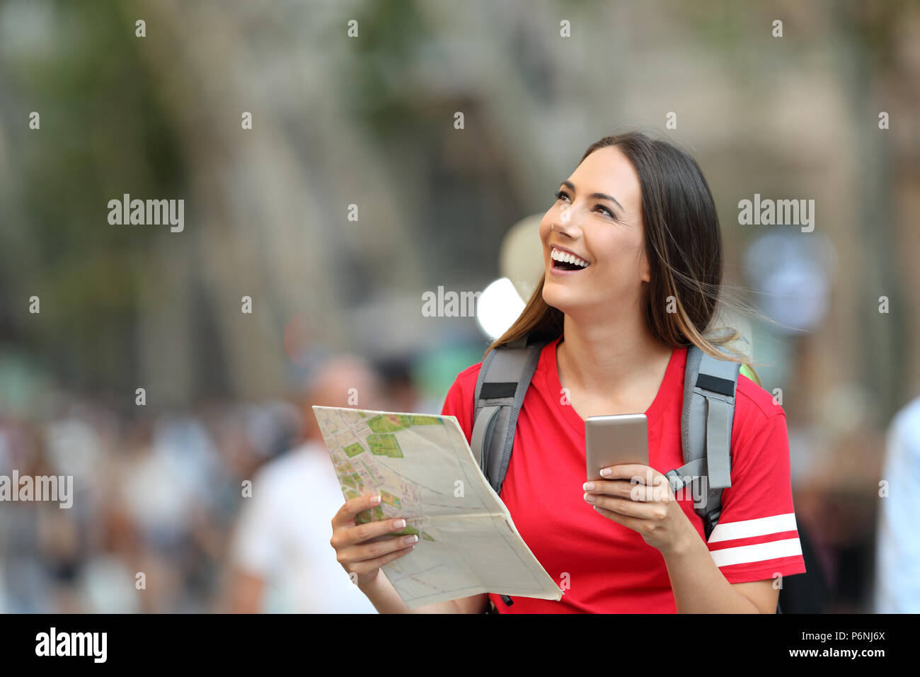 Teen tourist holding a paper guide and a smart phone looking above on the street - Stock Image