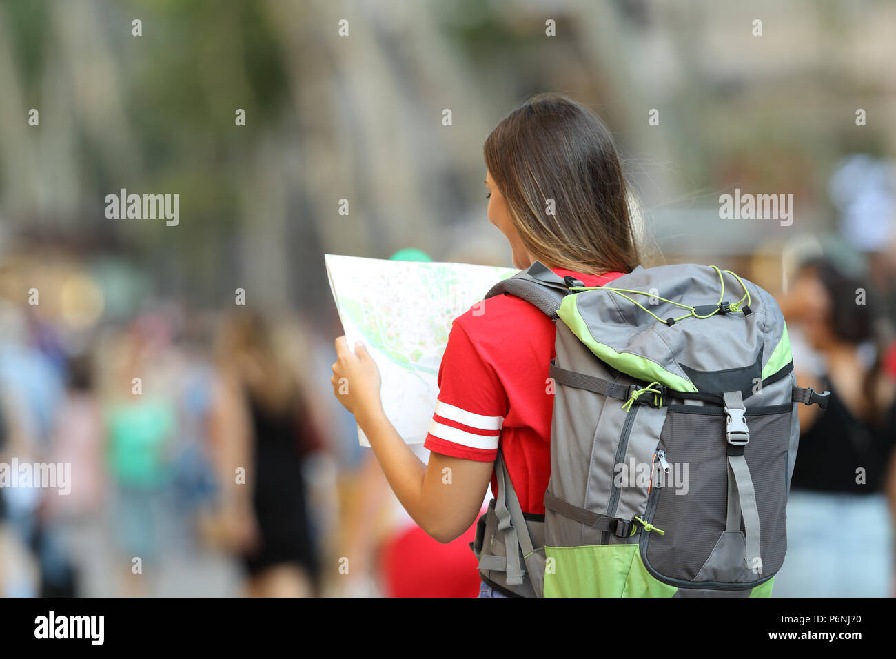 Back view of a teen tourist searching location in a paper map on the street - Stock Image