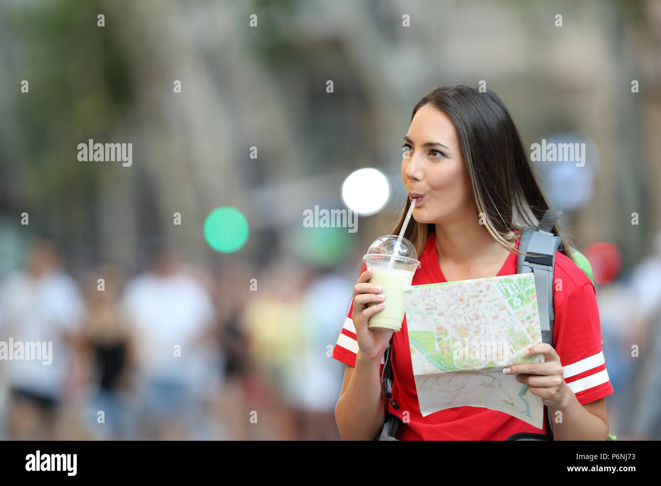 Teen tourist sightseeing drinking smoothie and holding a guide on the street - Stock Image