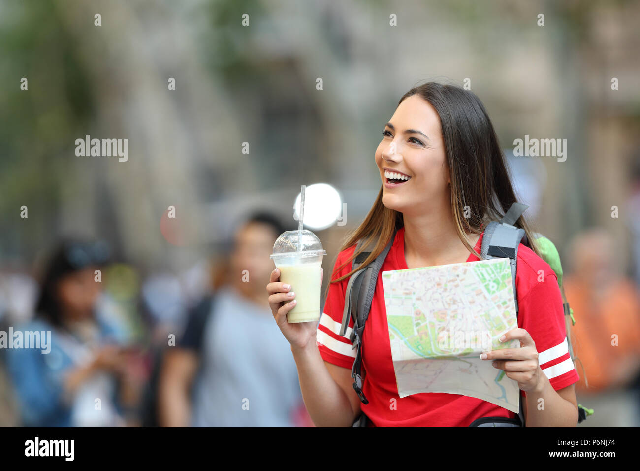 Happy teen tourist sightseeing holding a paper map in the street - Stock Image