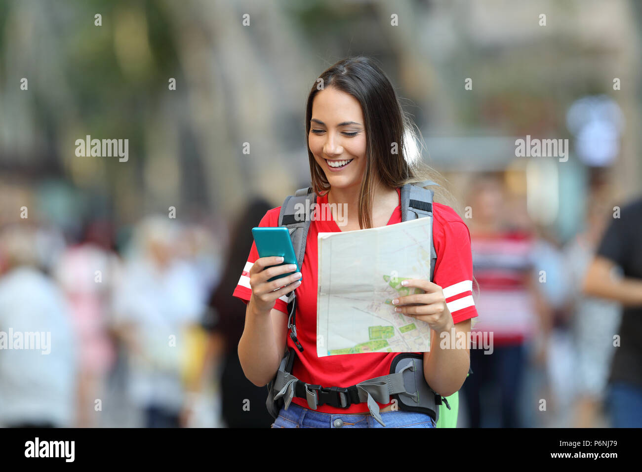 Happy teenage tourist searching destination online in a smart phone walking on the street - Stock Image