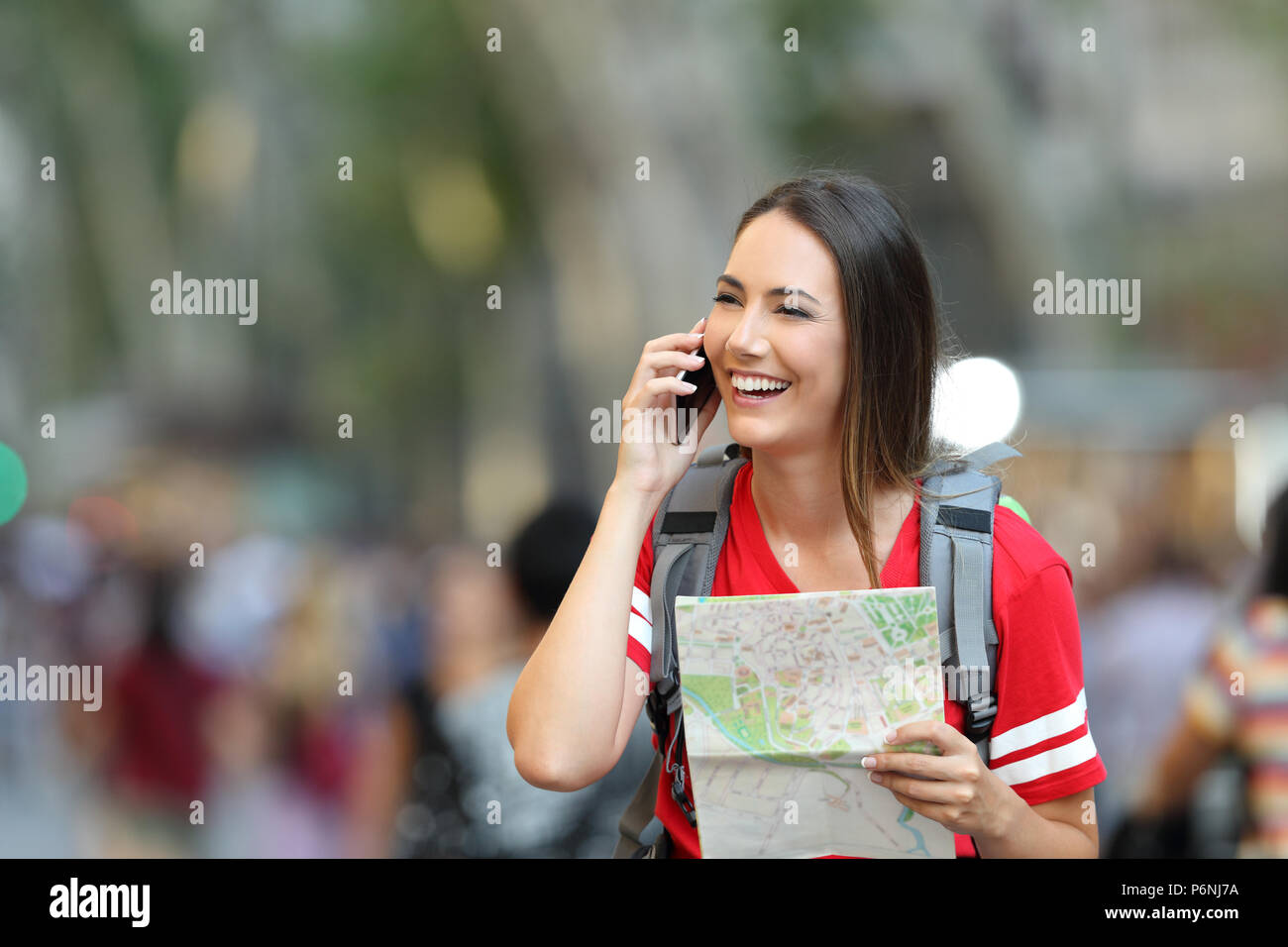 Teenage tourist talking on phone and holding a map in the street - Stock Image