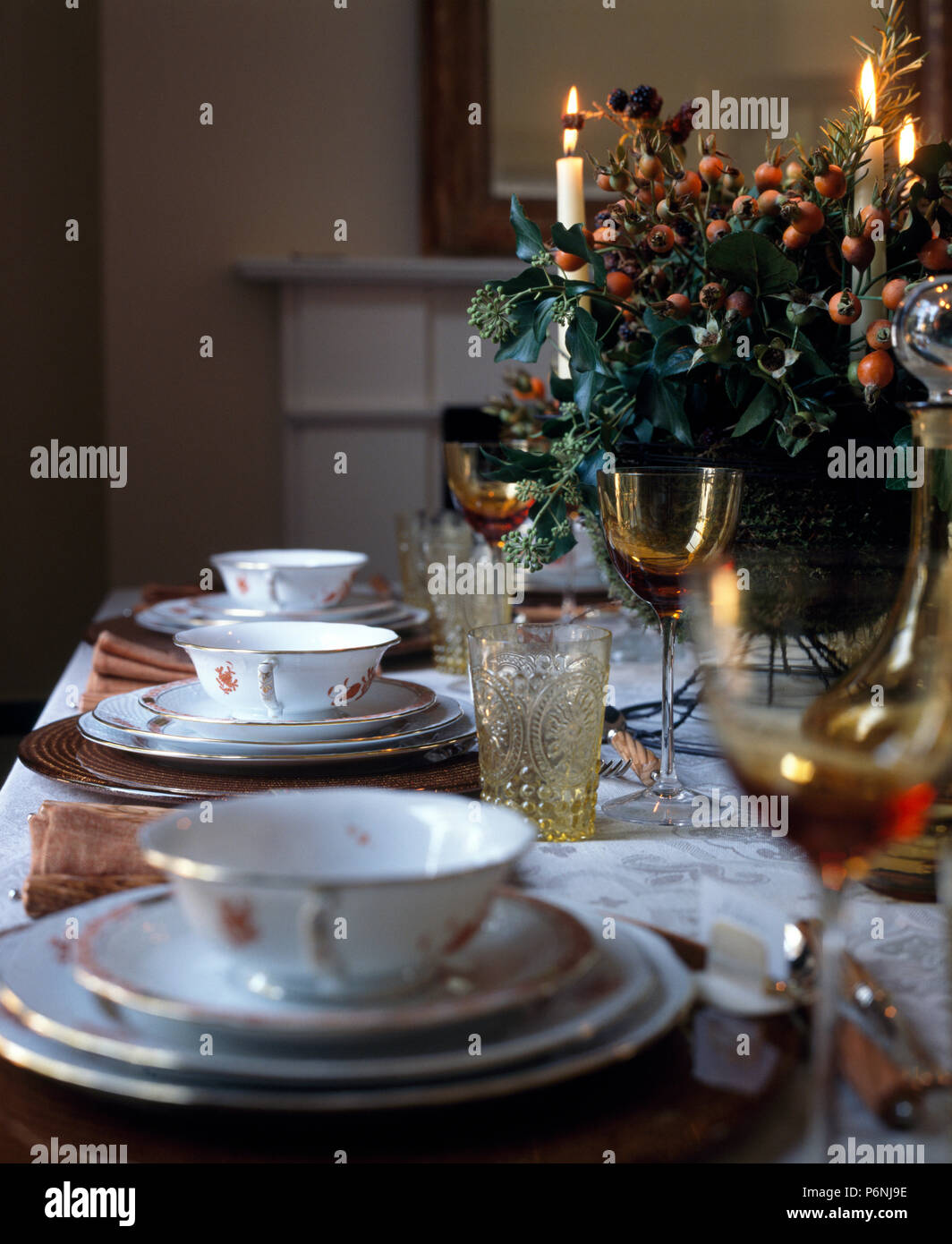 Close-up of vintage china soup bowls on a Christmas table set for dinner with lighted candles and festive floral display & Close-up of vintage china soup bowls on a Christmas table set for ...