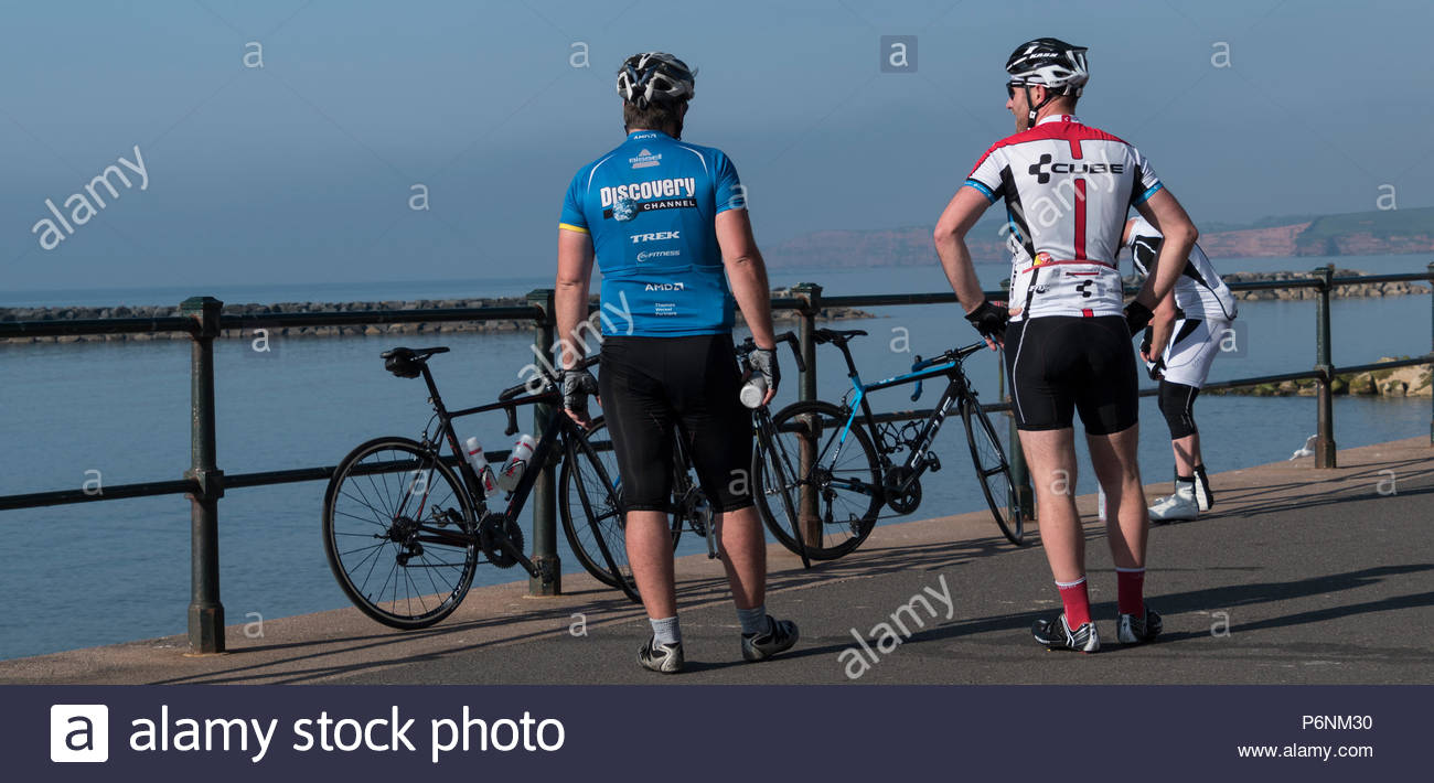 Several cyclists standing by their bikes on the seafront at Sidmouth, Devon, England, UK Stock Photo