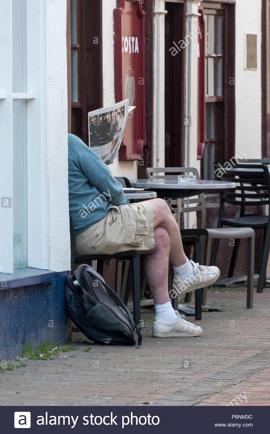 Man sat outside Coffee shop reading a newspaper. Sidmouth, Devon, England, UK Stock Photo