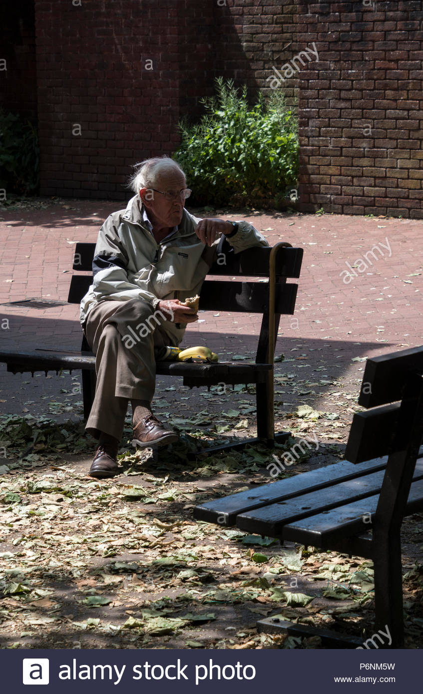 OAP eating lunch on a town centre bench, Ringwood, Hampshire, England, UK - Stock Image