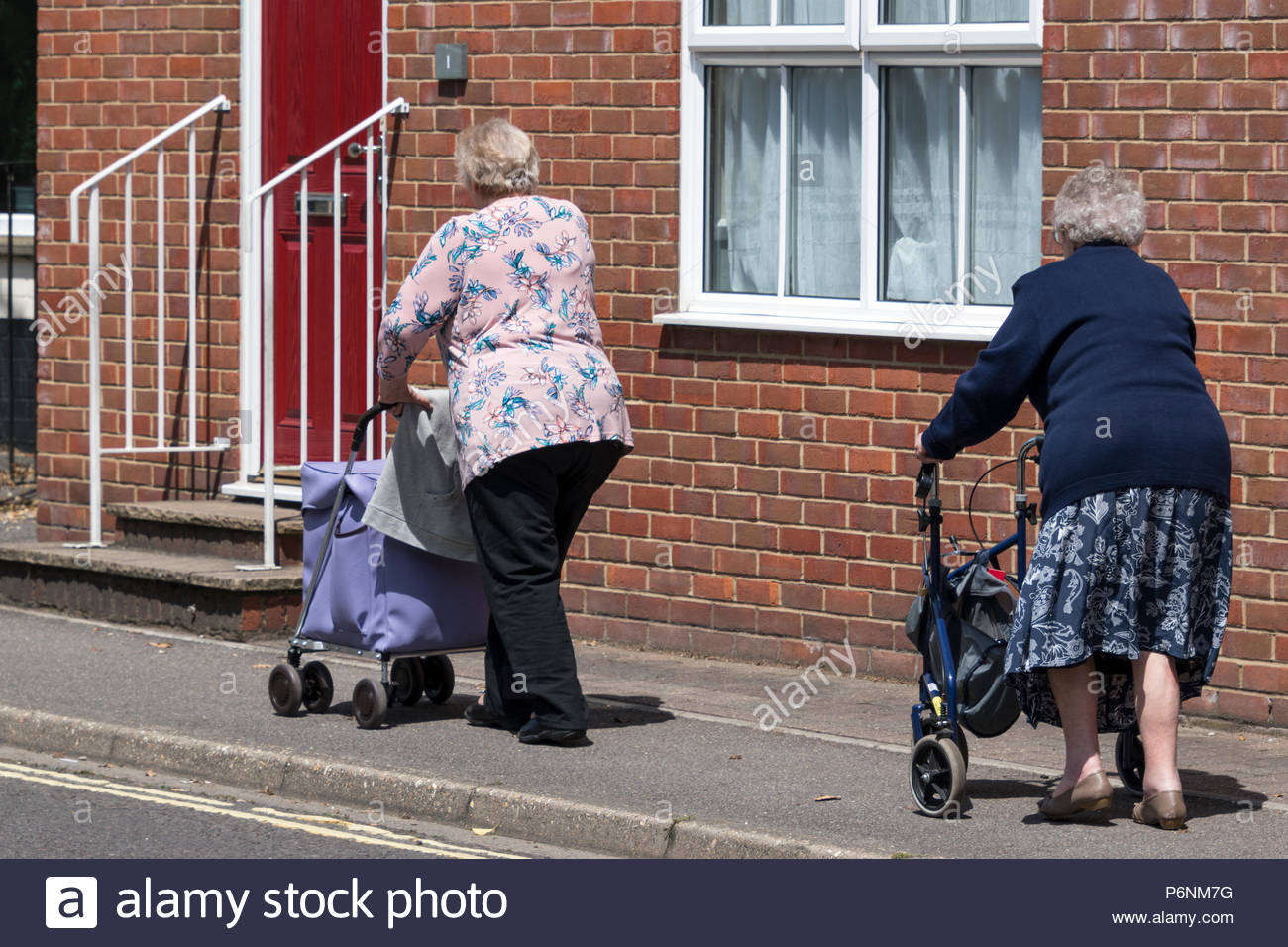 Rwo women, one with shopping trolley on with stroller along the street, Romsey, Hampshire, England, UK - Stock Image