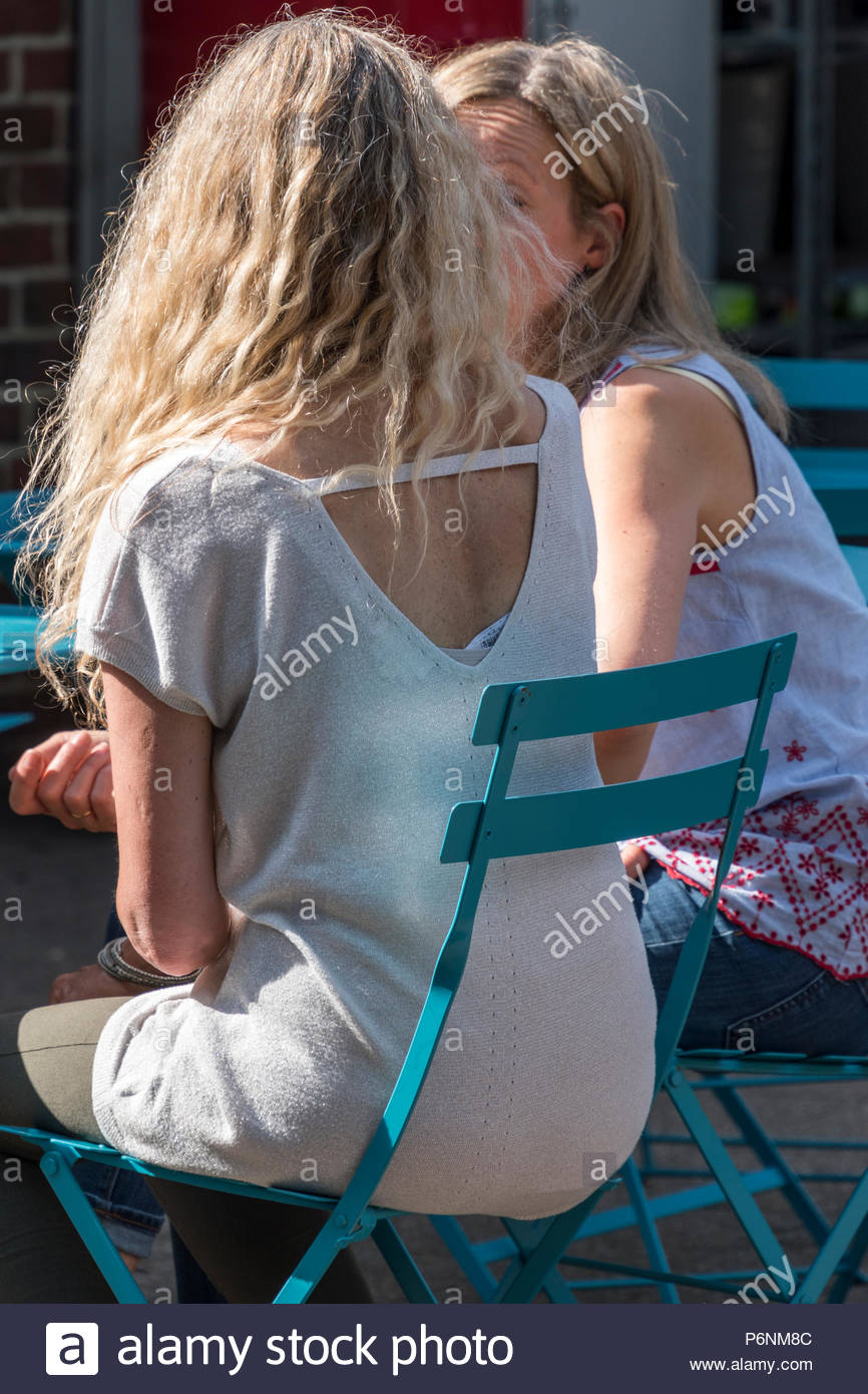 Two women chatting in the town centre, Ringwood, Hampshire, England, UK - Stock Image