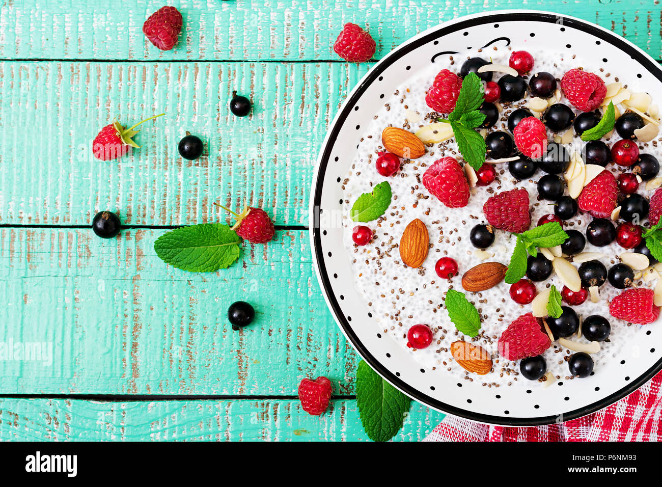 Detox and healthy superfoods breakfast in bowl. Vegan almond milk chia seeds pudding with raspberries, blackberries and  mint. Top view. Flat lay - Stock Image