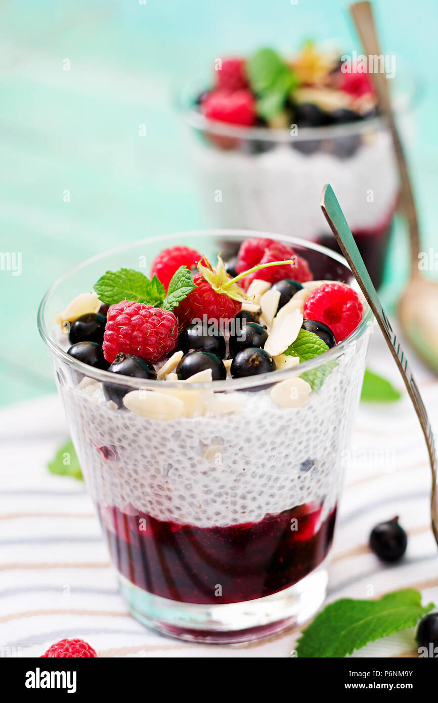 Detox and healthy superfoods breakfast in bowl. Vegan almond milk chia seeds pudding with raspberries, blackberries and  mint. - Stock Image