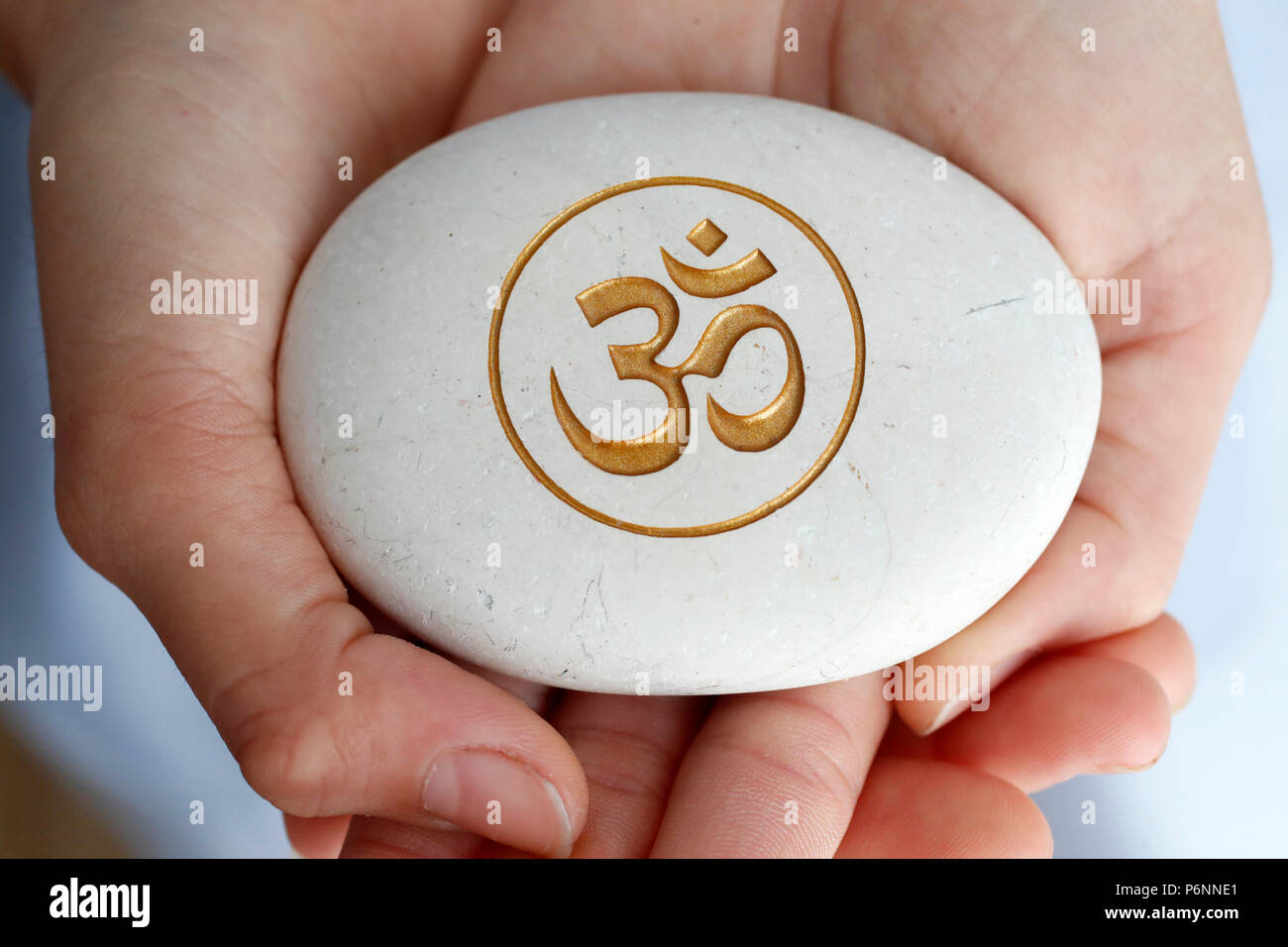 The Om or Aum symbol of Hinduism and Buddhism on a white stone. - Stock Image