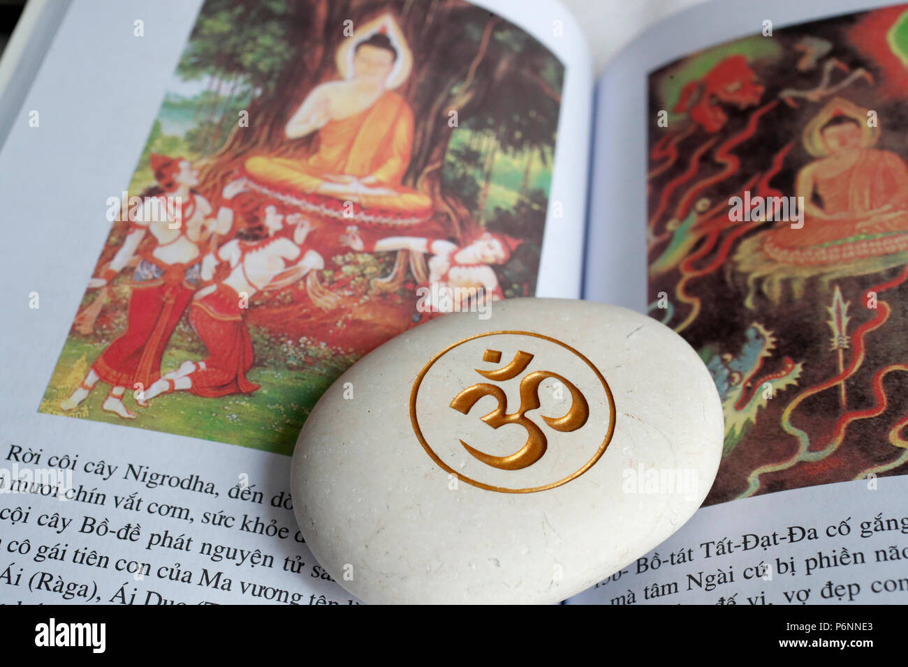 The Om or Aum symbol of Hinduism and Buddhism on a white stone. Book of the life of Buddha. - Stock Image