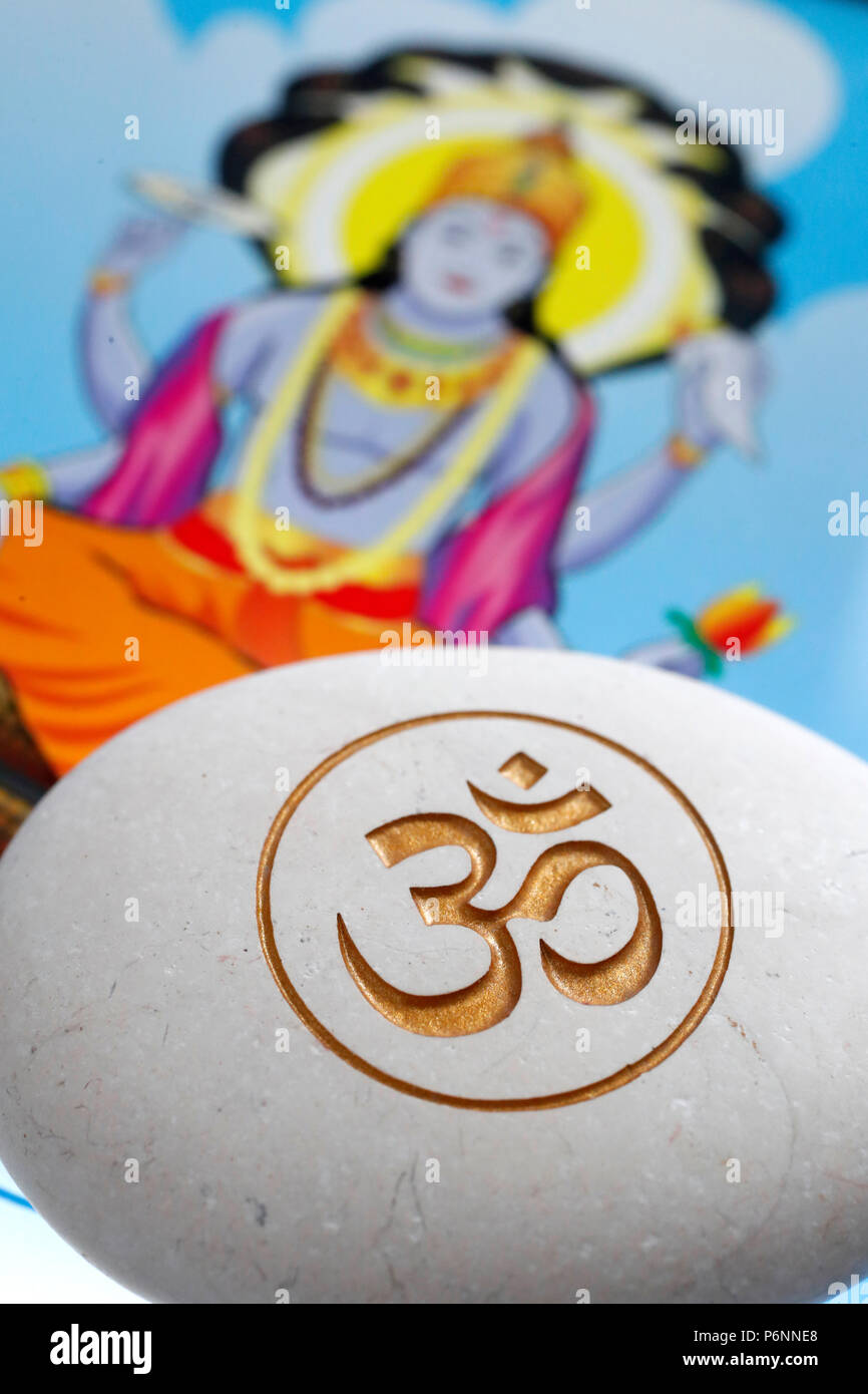 The Om or Aum symbol of Hinduism and Buddhism on a white stone.  Image of Vishnu on a tablet. - Stock Image