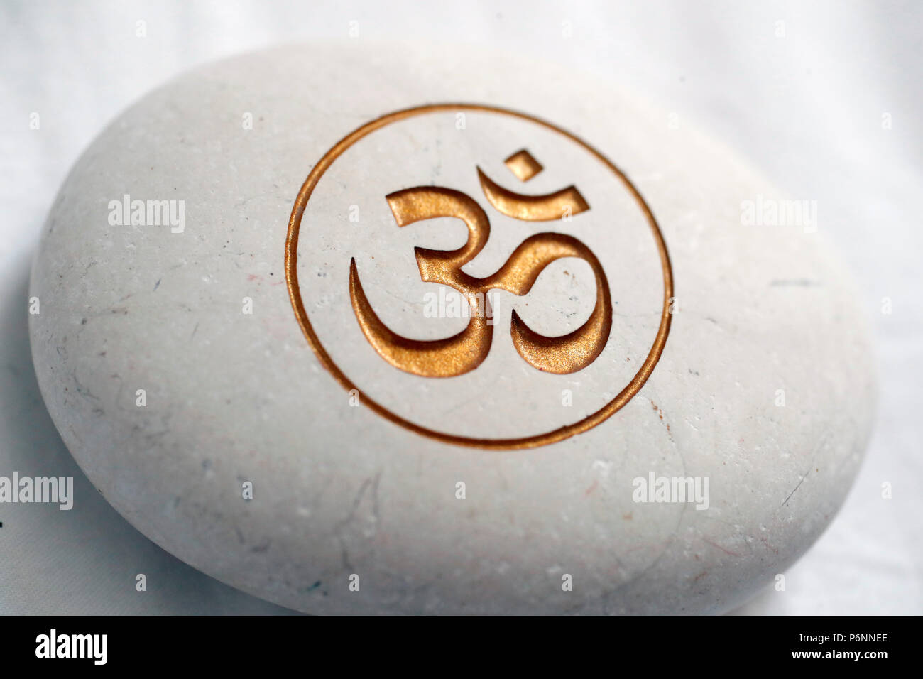 The Om Or Aum Symbol Of Hinduism And Buddhism On A White Stone Stock