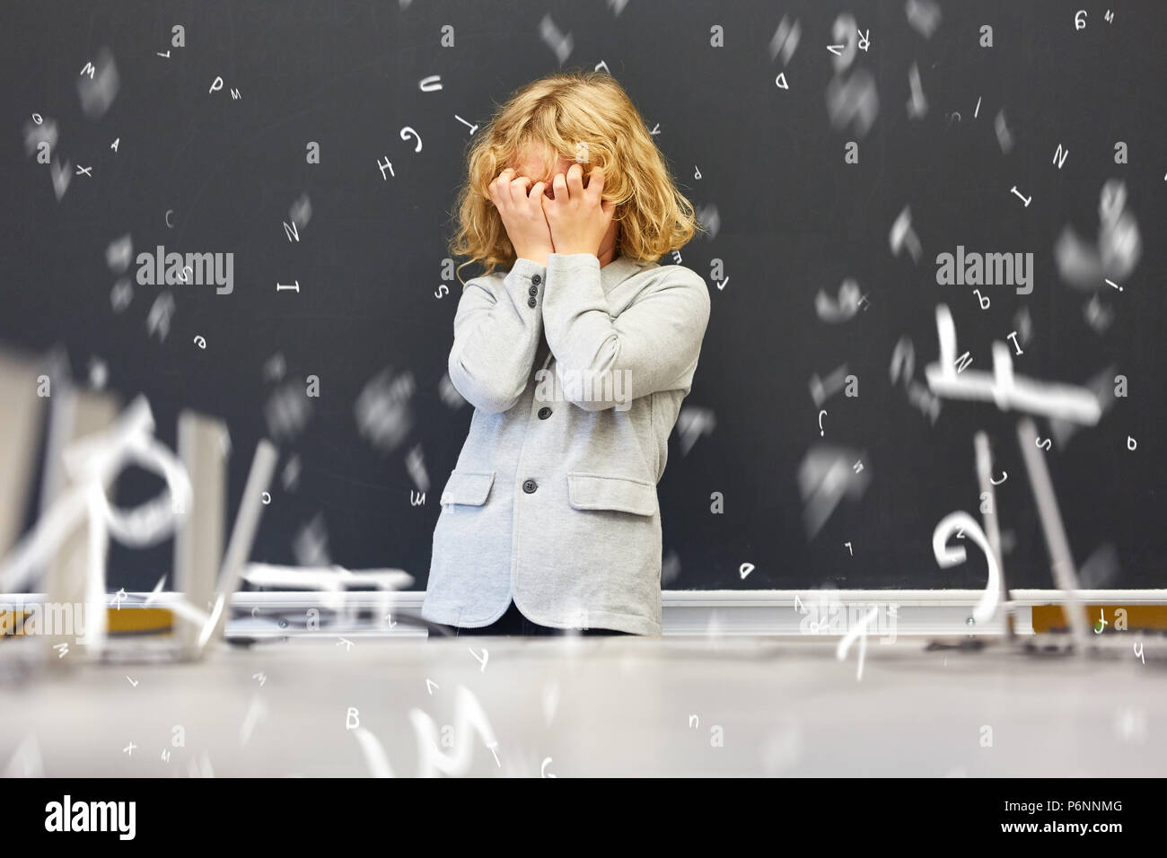 Frightened child with dyslexia in front of blackboard in elementary school - Stock Image