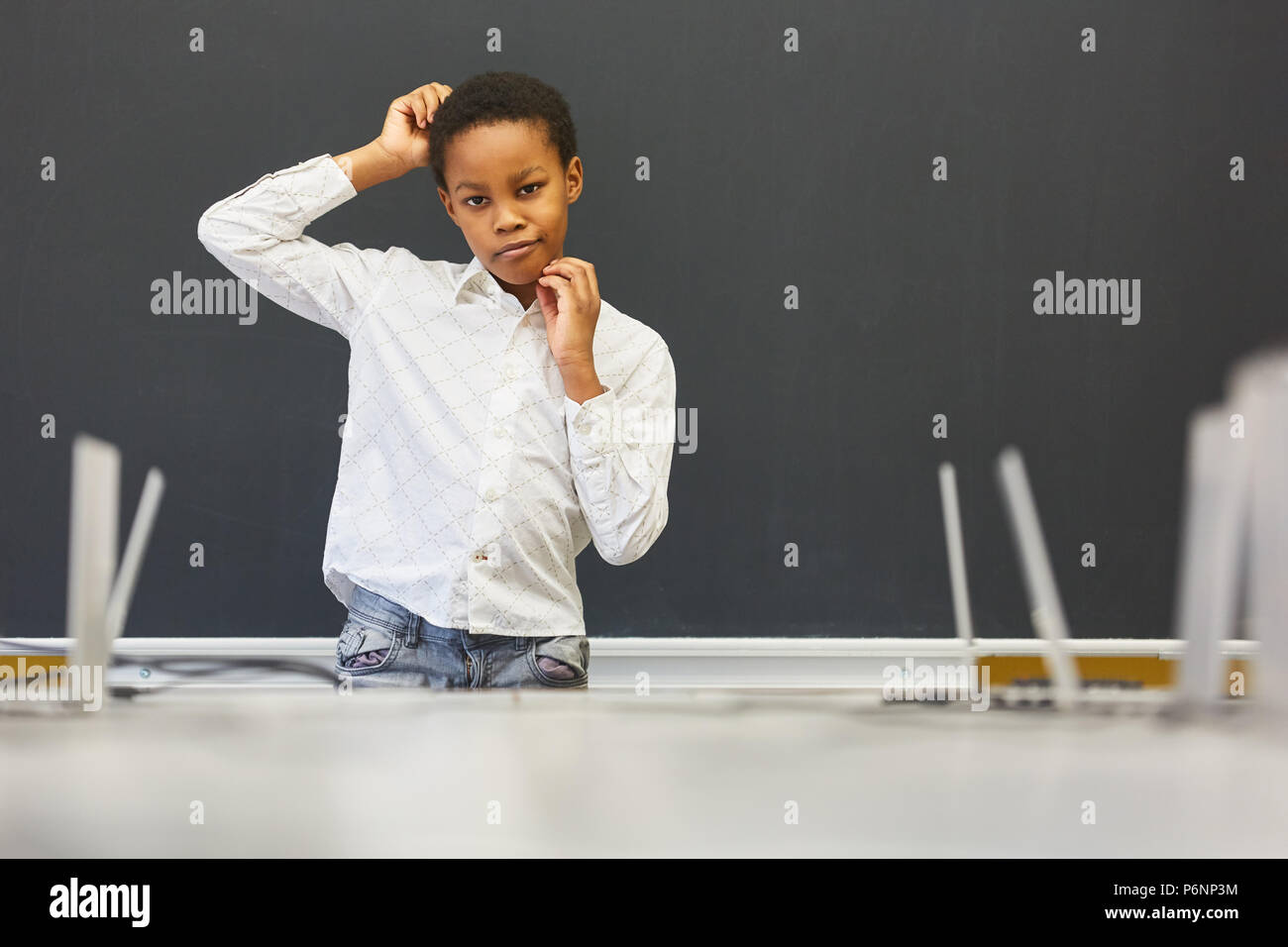 African child as a student scratches his head in a primary school exam - Stock Image