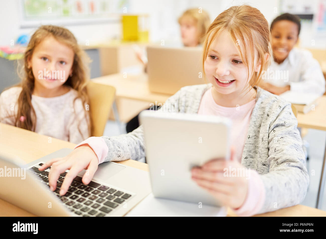 Kids in computer science learn lessons with laptop and tablet of