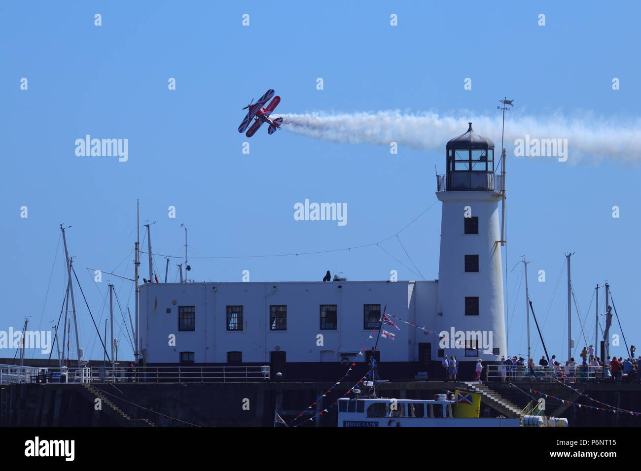 Rich Goodwin's Bi-plane flypasts the lighthouse during one of his acrobatic aerial displays at Scarborough Armed Forces Day. - Stock Image