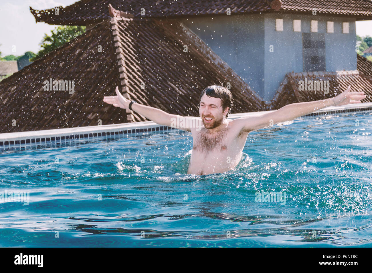 Portrait of happy smiling young man with hands up, which is bathed in pool on roof.  Emotions - joy, happiness, excited, positive, gleeful, glad - Stock Image