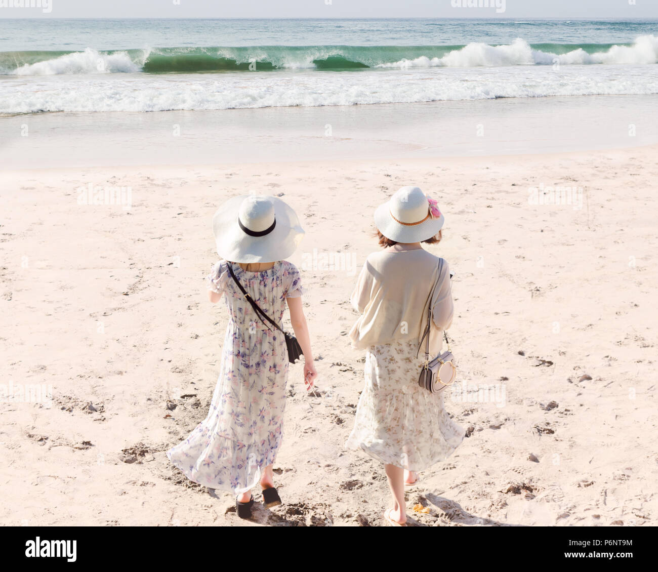 Rear view of two young women in long dresses and hats walking along sandy beach meet sea water. Bali island. Concept of wonderful holiday, escape - Stock Image