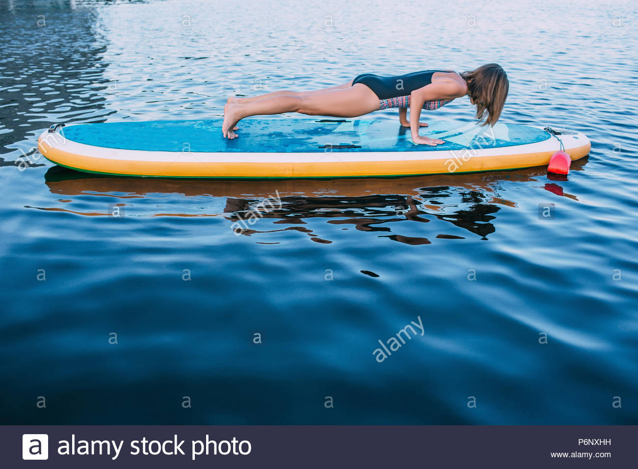 pretty sporty woman planking on paddleboard performing plank