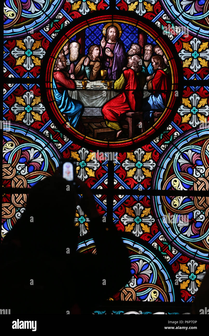 Basel Cathedral Minster. Stained glass window.  The Last Supper is the final meal that Jesus shared with his Apostles. Woman making picture. Switzerla - Stock Image