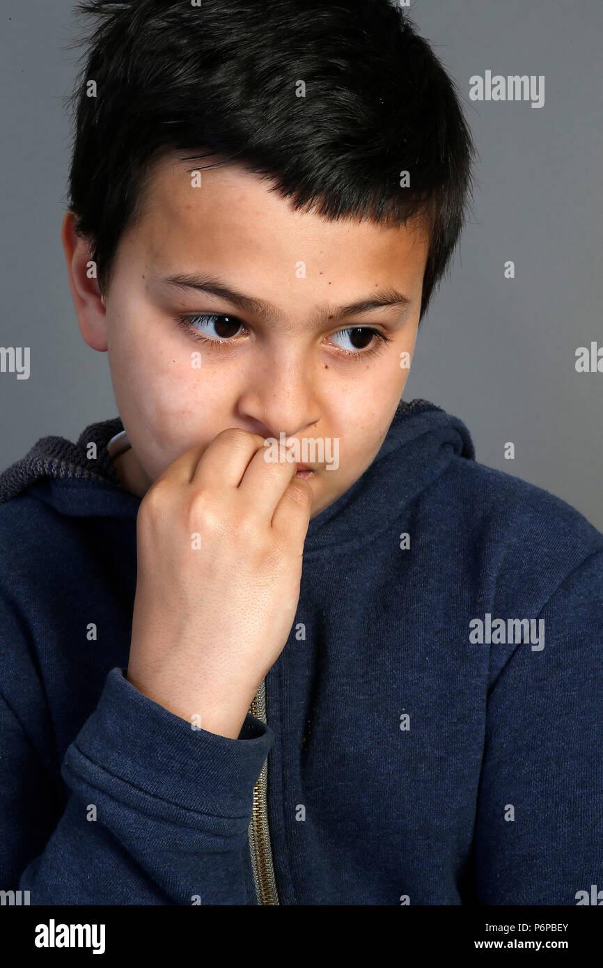12-year-old boy biting his nails. Paris, France. - Stock Image