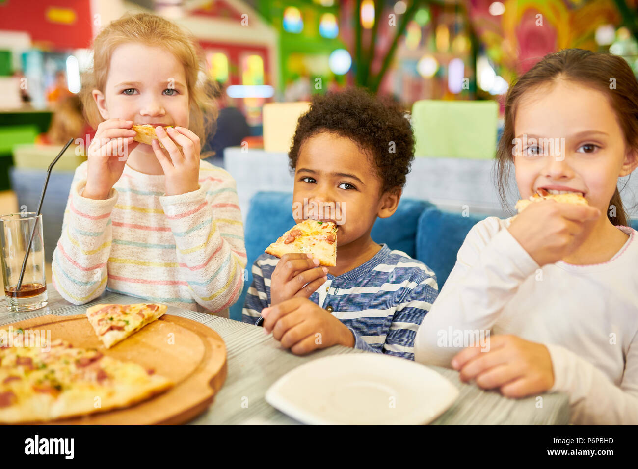 Children Eating Pizza in Cafe Stock Photo