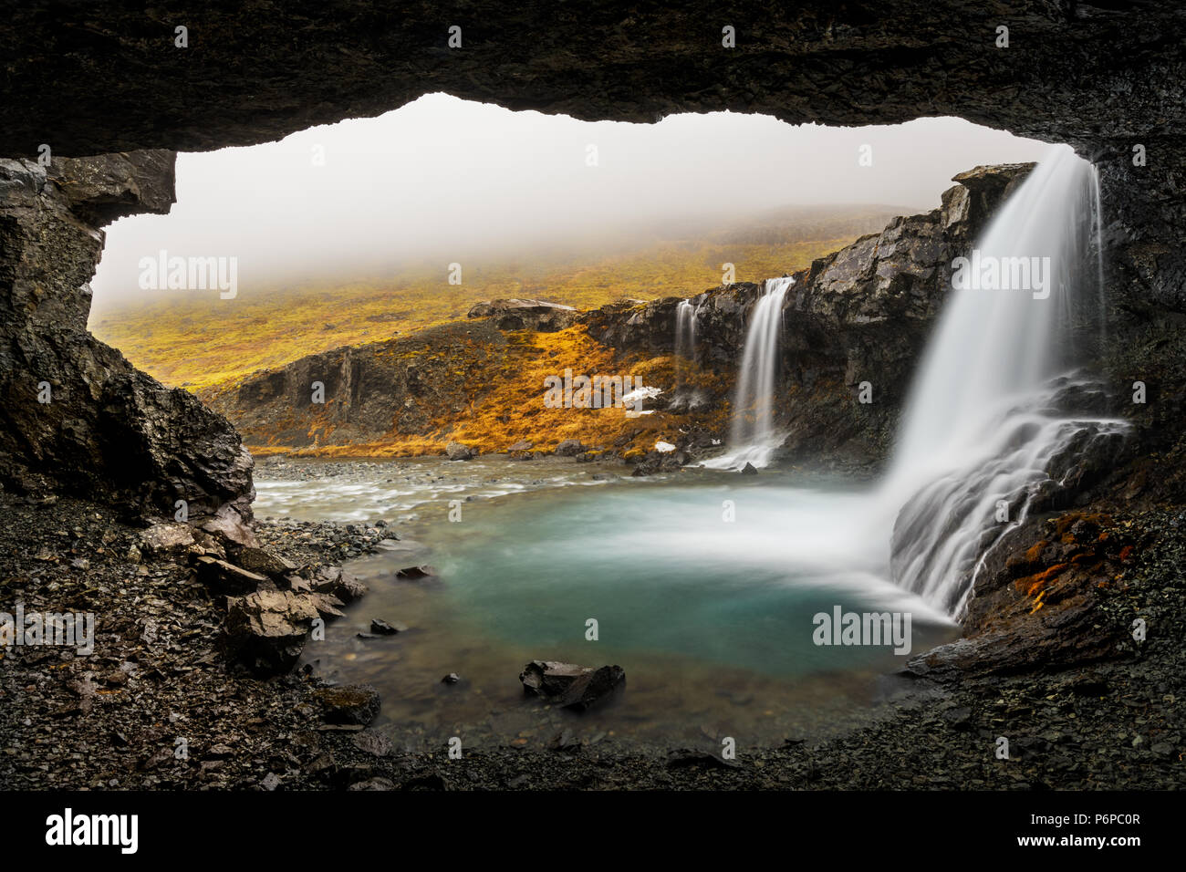 Low clouds hanging into Skutafoss on a rainy day. - Stock Image