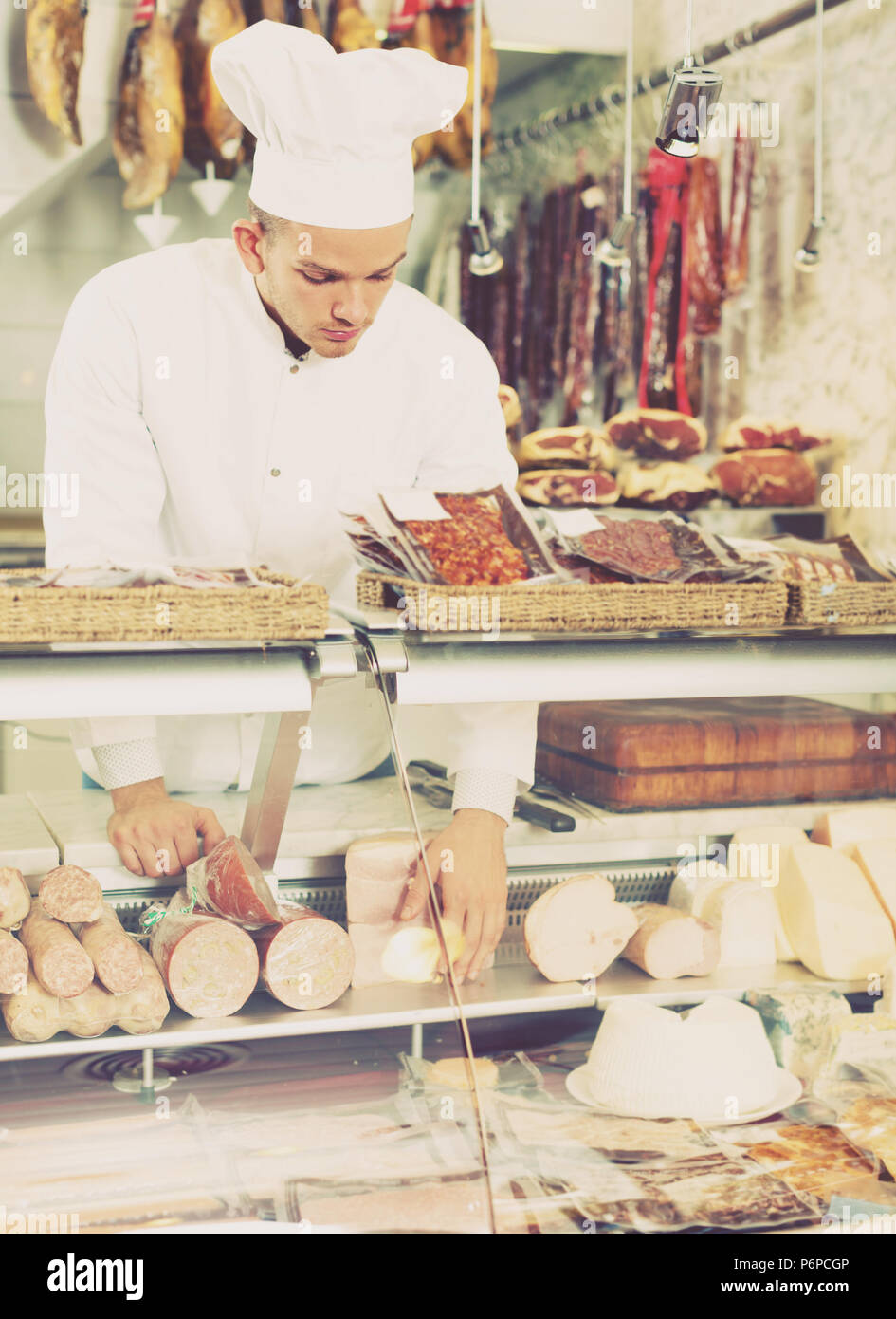 Positive seller in working clothes taking raw meat from stall - Stock Image